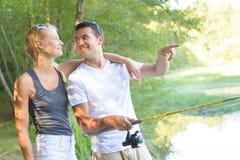 Jeune pêche de couples sur l'étang de banques Photos stock