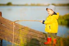 Jeune pêche de petit garçon de dock en bois Photographie stock