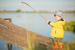 Jeune pêche de petit garçon de dock en bois Image stock