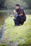 Jeune pêche ethnique heureuse de père et de fils Photographie stock libre de droits