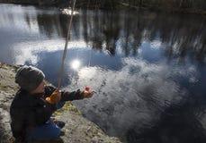 Jeune pêcheur vérifiant l'amorce Photo libre de droits