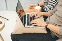 Jeune paiement asiatique de couples en ligne utilisant le coutil de achat de film d'ordinateur portable Image stock