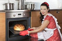 Jeune pain de cuisson de femme au foyer Image stock