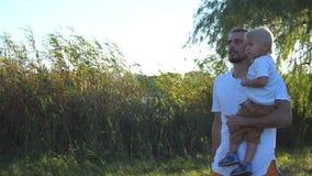 Jeune papa tenant son petit fils dans des mains et marchant au parc d'été un jour ensoleillé Famille heureuse passant le temps en clips vidéos