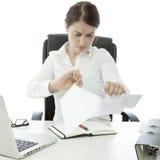 Jeune papier de larme de femme d'affaires sur son bureau Image stock