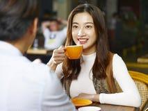Jeune parler asiatique de couples face à face dans le café Images stock