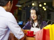 Jeune parler asiatique de couples face à face dans le café Photo libre de droits