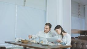 Jeune parler femelle au téléphone pendant le déjeuner et demande de son collègue masculin l'aide Image libre de droits