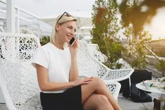 Jeune parler femelle au téléphone portable tout en se reposant dehors photos stock