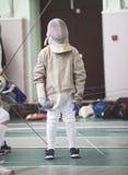 Jeune participant du tournoi de clôture dans des vêtements blancs et de masque protecteur sur le tournoi de clôture Photos stock