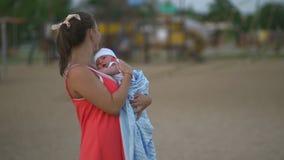 Jeune participation de mère et jeu avec son enfant de bébé garçon dans la position de parc de ville portant la robe rouge lumineu clips vidéos