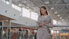 Jeune passager féminin à l'aéroport utilisant sa tablette tout en attendant le vol Image stock