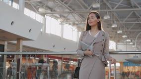 Jeune passager féminin à l'aéroport utilisant sa tablette tout en attendant le vol Photos stock