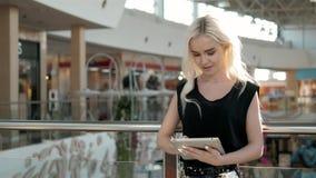 Jeune passager féminin à l'aéroport utilisant sa tablette tout en attendant le vol, belle femme de fille dedans Images stock
