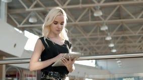 Jeune passager féminin à l'aéroport utilisant sa tablette tout en attendant le vol, belle femme de fille dedans Photo libre de droits