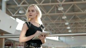 Jeune passager féminin à l'aéroport utilisant sa tablette tout en attendant le vol, belle femme de fille dedans Photo stock
