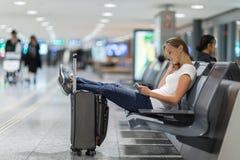 Jeune passager féminin à l'aéroport, utilisant son comprimé Photographie stock