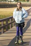 Jeune passerelle de croisement de l'adolescence sur des patins de poussette Photos stock
