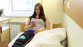 Jeune patient présentant l'eau potable de jambe et le téléphone blessés d'utilisation dans une chambre d'hôpital clips vidéos