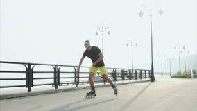 Jeune patinage de rouleau sportif d'homme sur le bord de mer d'été banque de vidéos