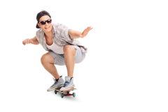 Jeune patineur joyeux montant une planche à roulettes photo libre de droits