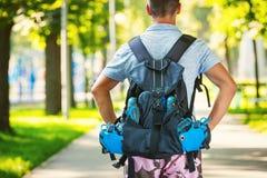 Jeune patineur masculin de rouleau avec le sac à dos de rouleau Image stock