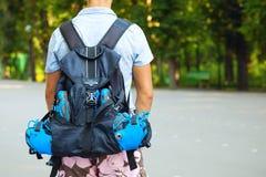 Jeune patineur masculin de rouleau avec le sac à dos de rouleau - pousse de behin Photos stock