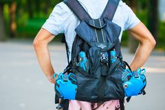 Jeune patineur masculin de rouleau avec le sac à dos de rouleau - pousse de behin Photographie stock