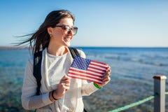 Jeune paysage admiratif de touristes femelle de la Mer Rouge et de tenir le drapeau des Etats-Unis sur le pilier Jour de la D?cla image stock