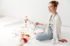 Jeune peintre caucasien heureux de dame s'asseyant à l'espace de travail Image stock