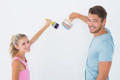 Jeune peinture de couples avec des brosses Photographie stock