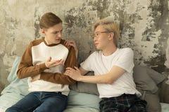 Jeune pensée masculine gaie songeuse triste à des problèmes de relations se reposant sur le lit avec l'ami offensé photo libre de droits