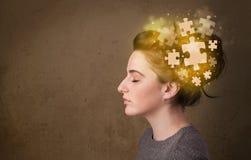 Jeune pensant avec l'esprit rougeoyant de puzzle Photographie stock libre de droits