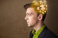 Jeune pensant avec l'esprit rougeoyant de puzzle Photos stock