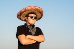 Jeune personne masculine dans le sombrero et des lunettes de soleil dans le backgr clair de ciel photographie stock
