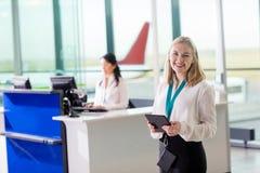 Jeune personnel au sol tenant la Tablette de Digital à l'aéroport photographie stock libre de droits