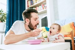 Jeune petit déjeuner mangeur d'hommes beau et alimentation de son bébé à la maison photos libres de droits