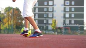 Jeune petit garçon jouant dans le domaine avec du ballon de football Concept de sport banque de vidéos