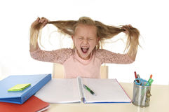 Jeune petite écolière douce tirant ses cheveux désespérés dans l'effort tandis que se reposer sur le bureau d'école faisant des d image stock