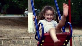 Jeune petite fille heureuse tournant dans une oscillation et un sourire banque de vidéos