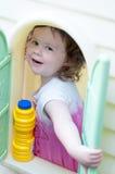 Jeune petite fille jouant dans la maison de jouet dans l'arrière-cour un jour ensoleillé Images libres de droits