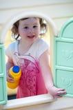 Jeune petite fille jouant dans la maison de jouet dans l'arrière-cour un jour ensoleillé Photos stock