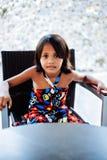 Jeune petite fille mignonne s'asseyant sur la seule attente de chaise Photos stock