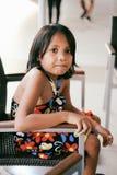 Jeune petite fille mignonne s'asseyant sur la seule attente de chaise Image libre de droits