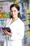 Jeune pharmacien beau avec un comprimé dans une pharmacie Images stock