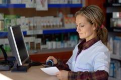Jeune pharmacien féminin tenant la prescription Photographie stock libre de droits