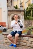 Jeune photographe avec la photo andtaking de banc de pierre de laptopon sur l'appareil-photo Photo libre de droits