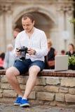 Jeune photographe avec la photo andtaking de banc de pierre de laptopon sur l'appareil-photo Images libres de droits