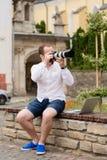Jeune photographe avec la photo andtaking de banc de pierre de laptopon sur l'appareil-photo Photos stock