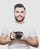 Jeune photographe barbu prenant des photos avec l'appareil photo numérique Images stock